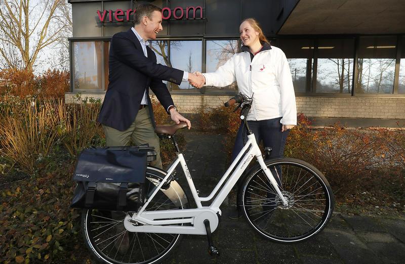 Sten van der Ham van Accell Benelux (links) reikt de eerste zorgfiets uit aan wijkverpleegkundige Angela Roos van Vierstroom Zorg Thuis.