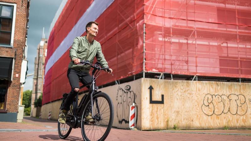 fiets van de zaak met berijder en rode muur